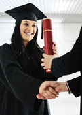 Young female graduating and receiving diploma at university — Stock Photo