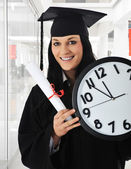 Graduating girl with diploma holding a watch — Stock Photo