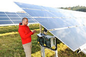 Engineer working with laptop by solar panels, talking on cell phone — Zdjęcie stockowe