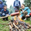 Barbecue in nature, group of preparing sausages on fire (note: selected focus) - Stock Photo