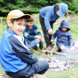 Stock Photo: Barbecue in nature, group of children preparing sausages on fire