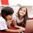 Stock Photo: Little girl and boy lying with laptop at home on the ground
