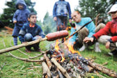 Barbecue in nature, group of preparing sausages on fire (note: selected focus) — Stock Photo