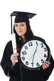 Graduate girl student in gown with diploma and clock — Stock Photo