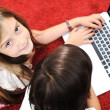 Stock Photo: Little girl and boy lying with laptop at home on ground