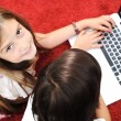 Little girl and boy lying with laptop at home on the ground — Stock Photo