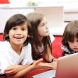 Stock Photo: Three children lying with laptop at home on ground
