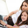 Mother and daugther with laptop on sofa — Stock Photo #21370181