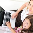 Mother and daugther with laptop on sofa — 图库照片