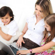 Stock Photo: Mother with daugther and son using laptop on sofa indoor