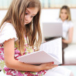 Little girl reading in home, indoor with happy family — Stok fotoğraf