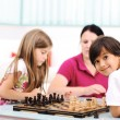 Little brother and sister playing chess at home with their mother — Stock Photo
