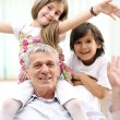 Grandfather with children, senior man at home with family — Stock Photo