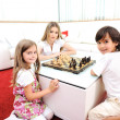 Happy family at home, young mother playing chess with her children — Stok fotoğraf
