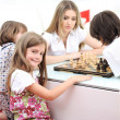 Happy family at home, young mother playing chess with her children — Foto de Stock