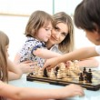 Stock Photo: Happy family at home, young mother playing chess with her children