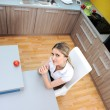 Стоковое фото: Young beautiful blonde woman in kitchen sitting on chair