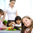 Foto Stock: Happy family in the kitchen, mother and children cooking together