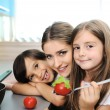 Happy children with their mother in the kitchen together — Stock Photo #21373217