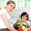 Beautiful mother and little son in kitchen together — Stock Photo