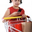 Little girl shopper in red dress with shopping cart — Stock Photo