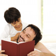 Father and son in bed, reading book together — Stock Photo