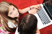 Little girl and boy lying with laptop at home on the ground — Stockfoto