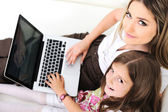 Mother and daugther with laptop on sofa — Stock Photo