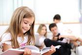 Menina lendo em casa, interior com a família feliz — Foto Stock