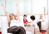 Rilassata giovane donna stretchin sul divano di casa — Foto Stock