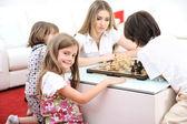 Família feliz em casa, jovem mãe jogando xadrez com seus filhos — Fotografia Stock