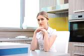 Donna bionda bella giovane in cucina, seduto sulla sedia — Foto Stock