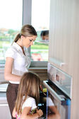Young mother and little girl daughter in kitchen — Stock Photo