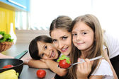Happy children with their mother in the kitchen together — Stock Photo