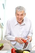 Good looking senior man working in kitchen — Stock Photo