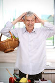 Good looking elderly man cooking in kitchen — Stock Photo