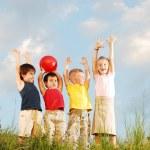 Happy children raising hands upwards — Stock Photo #21404253
