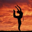 Sport acrobatic girl against fantastic red sky — Stockfoto