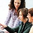 Stock Photo: While meeting, group of young women working together on the table