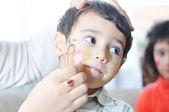Positieve kind met kleuren op zijn gezicht en lichaam — Stockfoto