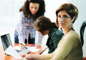 Female executive giving presentation to her colleagues — Stock Photo
