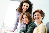Podczas spotkania, grupa młodych kobiet pracujących razem na stole — Zdjęcie stockowe