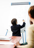 Genius kid on business presentation speaking to adults and giving them a lecture — Stock Photo