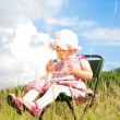 Baby girl siting in nature and drinking milk from bottle — Stock Photo