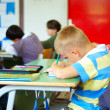 Blond cute kid in classroom writting — Zdjęcie stockowe #21447477
