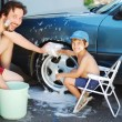 Child washing car and toy car with his father — Stock Photo #21448609