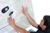 Man pointing on maps — Stock Photo