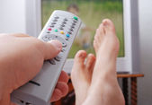Remote control in hand headed into television — Stockfoto