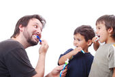 Father teaching his two sons how to clean the teeth — Stock Photo
