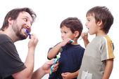 Ung man lära barn hur man rengör tänderna — Stockfoto